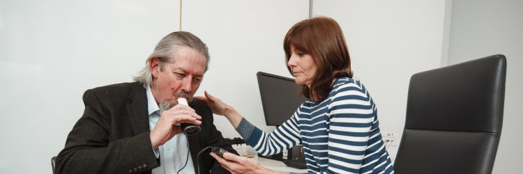 research nurse doing a breath test with a patient